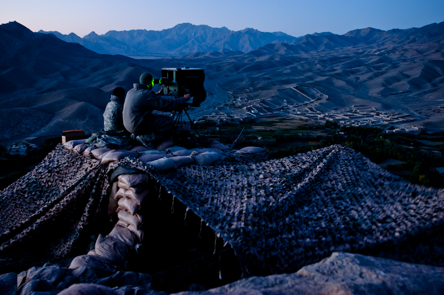 Soldiers use a high-powered night vision device to scan the main road of the Tangi Valley from a mountaintop observation post. The soldiers are looking for insurgents planting IEDs in a road where there have been dozens of attacks since Apache Company arrived in summer 2009.