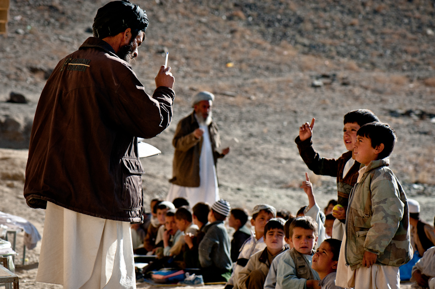 Children ask their teacher questions at an all boys' school in the Tangi Valley, Wardak Province, Afghanistan. As winter neared, in October 2009, the teachers of the school sought building materials from the US Army unit stationed nearby in order to fortify their school; as of October, students were still studying outside. There are no girls' schools in the Tangi Valley.