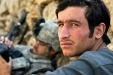 A US Army soldier, background, registers biometric data of the young Afghan man in the foreground.