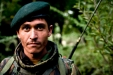 An Afghan National Army radio operator surrounded by apple groves and brush on a morning mission in the Jalrez Valley.