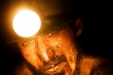 Workers labor by the light of headlamps in the Karkara coalmine.