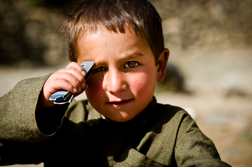 A small boy looks on as US Army soldiers and Afghan National Police search his family compound in the Jalrez Valley, Wardak Province, Afghanistan.