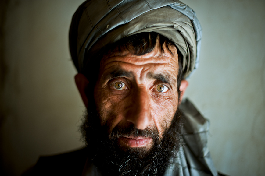A village elder in the Jalrez Valley looks on as US Army soldiers and Afghan National Police search his family compound.