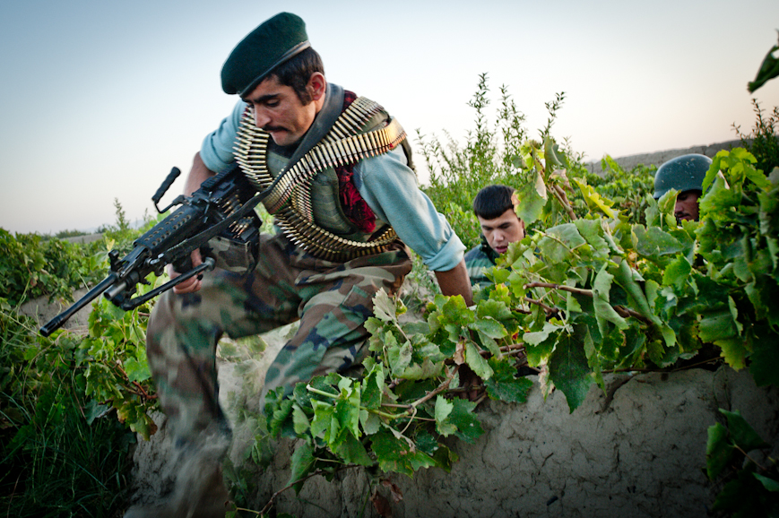 An Afghan National Army soldier jumping a wall in a grape vineyard in Arghandab District, Kandahar Province.
