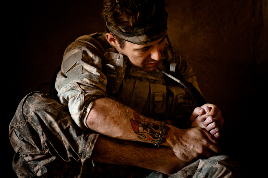 "Sergeant Josh Strickland inspects his damaged feet during a pause in patrolling on the second day of the operation to Nur Muhammad Kalache, 31 August. Strickland stepped on a ""toe-popper,"" a small IED designed to maim but not kill, moments before; however, only the ignition charge went off, not the main charge. The result was that Strickland's toe was severely bruised, but remained on his foot."