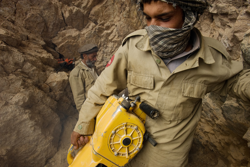 Panjshir, Afghanistan: Izhak, 22, Commander Jalaluddin's son, carrying his drill in the emerald mine. July 2010.